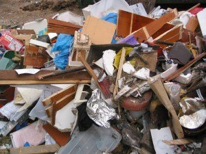 heavy rubbish being thrown into an 8m skip bin to be taken to the dump